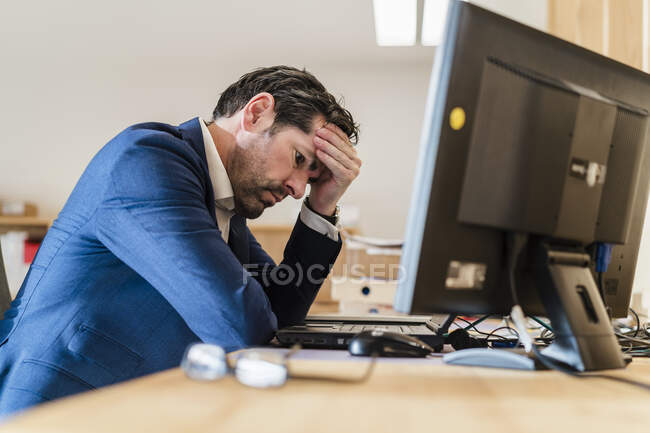 Hombre de negocios frustrado sentado en el escritorio en la oficina - foto de stock