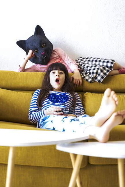 Due ragazze annoiate sedute sul divano, a guardare la TV, una con la maschera da gatto — Foto stock