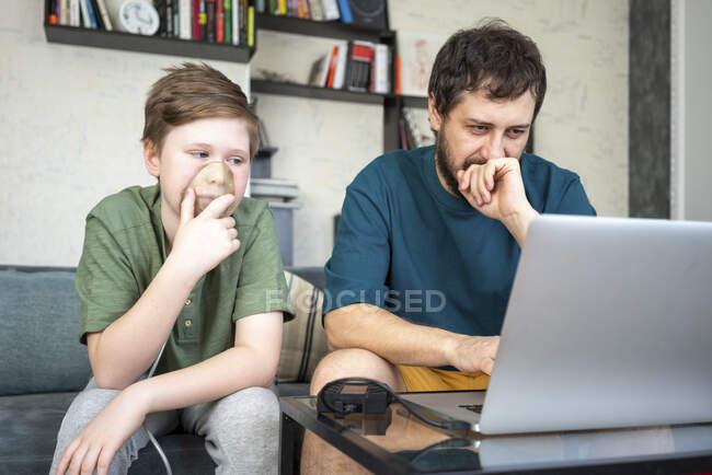 Портрет батька і сина, які сидять разом на дивані за допомогою ноутбука. — стокове фото