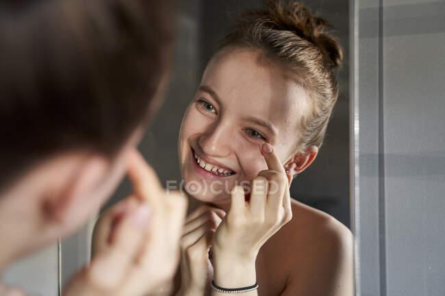 Дзеркальний образ смішної дівчинки, що використовує крем для обличчя у ванній кімнаті. — стокове фото