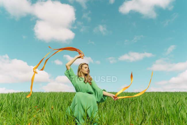 Молода жінка в зеленій сукні сидить на полі з дувними стрічками. — стокове фото