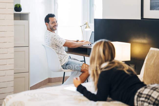 Улыбающийся мужчина смотрит на свою девушку, сидя за столом с ноутбуком — стоковое фото