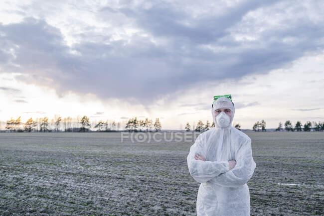 Hombre con traje protector y máscara de pie en el campo — Stock Photo