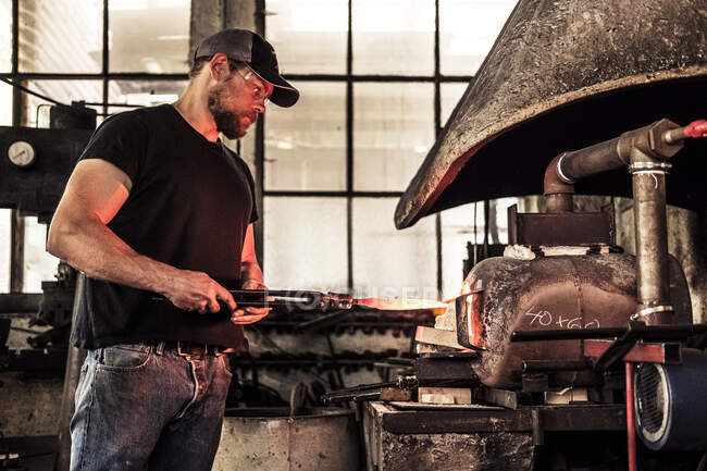 Knife maker working with damask steel at forging furnace — Stock Photo
