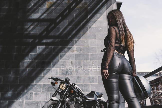 Сексуальная молодая женщина с мотоциклетным шлемом, стоящая у мотоцикла, вид сзади — стоковое фото