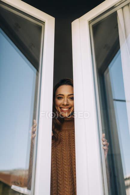 Retrato de una joven feliz en la ventana - foto de stock