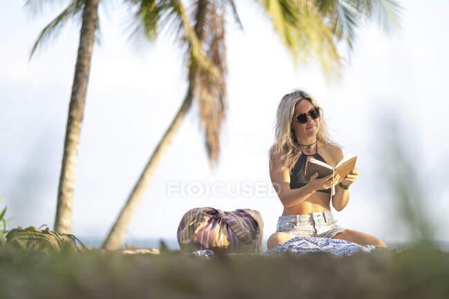 Hermosa mujer leyendo un libro en la playa, Costa Rica - foto de stock