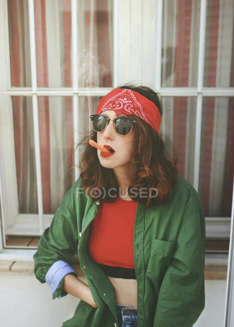 Retrato de mujer joven con diadema y gafas de sol fumando zanahoria - foto de stock