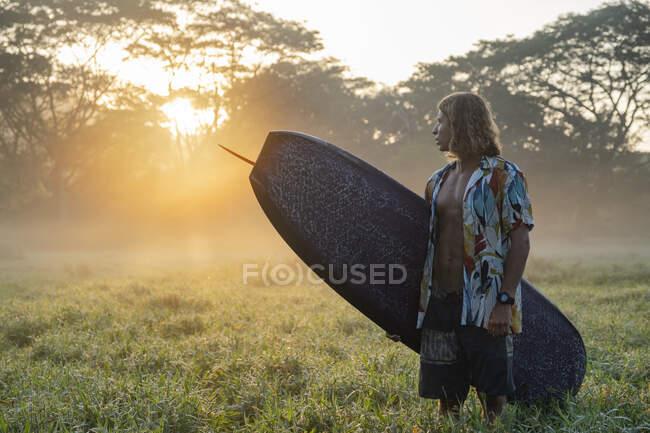 Joven con tabla de surf de pie en un prado al amanecer, Costa Rica - foto de stock