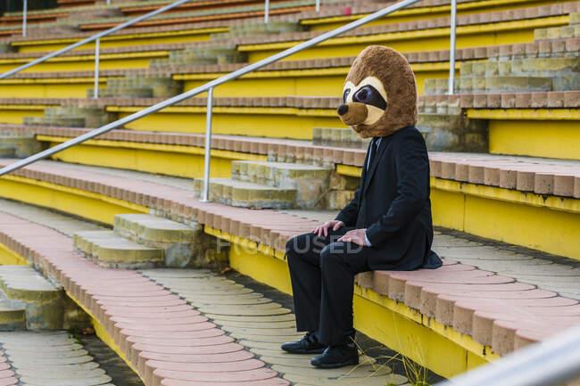 Empresario en traje negro con máscara de suricata sentado solo en las escaleras - foto de stock