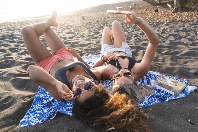 Dos mujeres felices tumbadas en la playa escuchando música por teléfono, Costa Rica - foto de stock