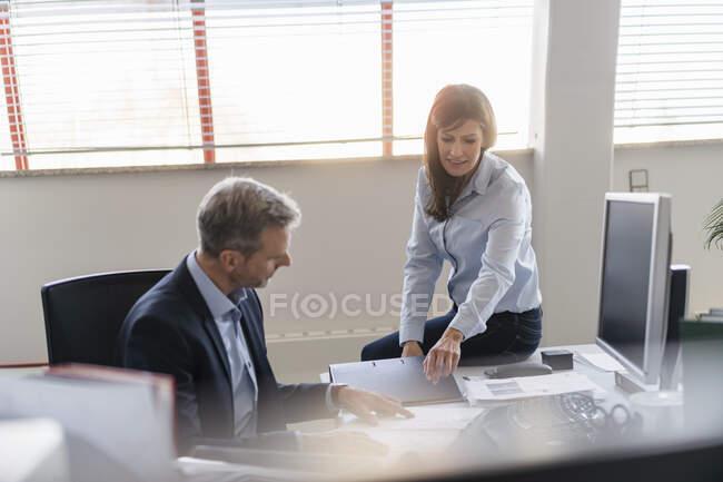 Homme d'affaires et femme d'affaires parlant au bureau au bureau — Photo de stock