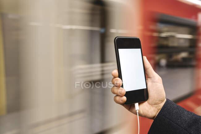 Primer plano del hombre sosteniendo el teléfono inteligente en la estación de metro - foto de stock