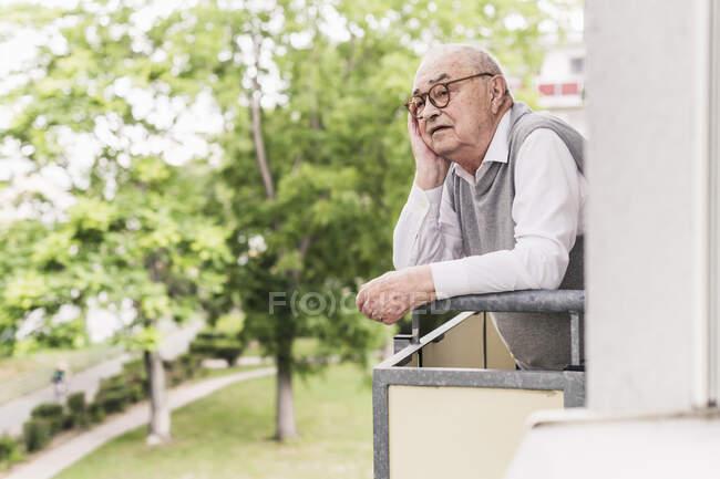 Retrato de homem sênior em pé na varanda olhando para a distância — Fotografia de Stock