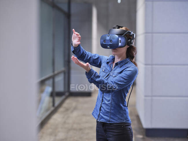 Woman wearing VR glasses and headset in modern office — Stock Photo