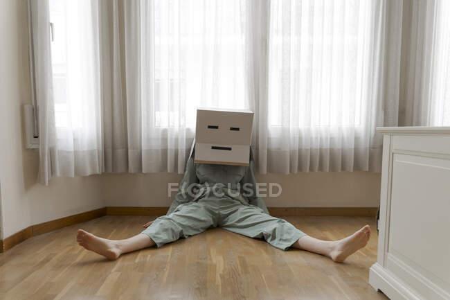 Mujer con una caja de cartón en la cabeza con sonrisa aburrida sentada en el suelo - foto de stock