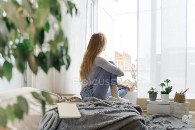 Молодая женщина дома смотрит в окно — стоковое фото