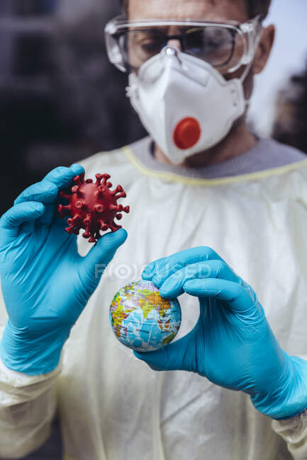 Працівник охорони здоров'я тримає модель Corona Virus і міні-глобус — стокове фото