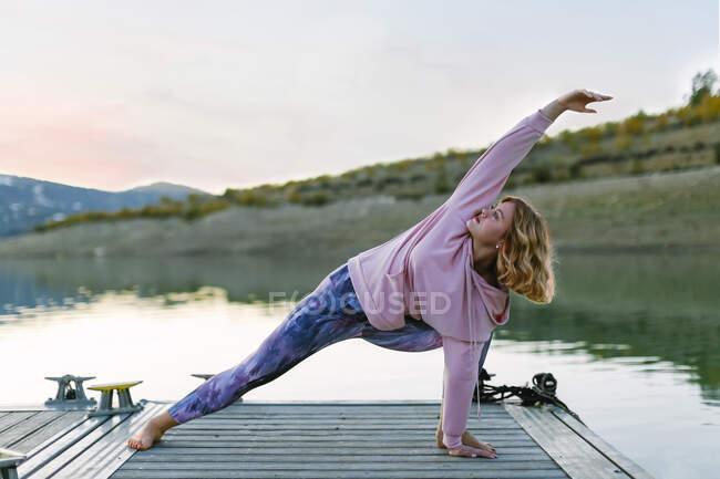 Молодая женщина, занимающаяся йогой на причале, в треугольной позе — стоковое фото