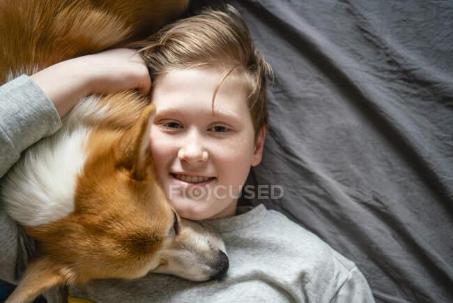 Retrato de niño sonriente acostado en la cama abrazando a su perro - foto de stock