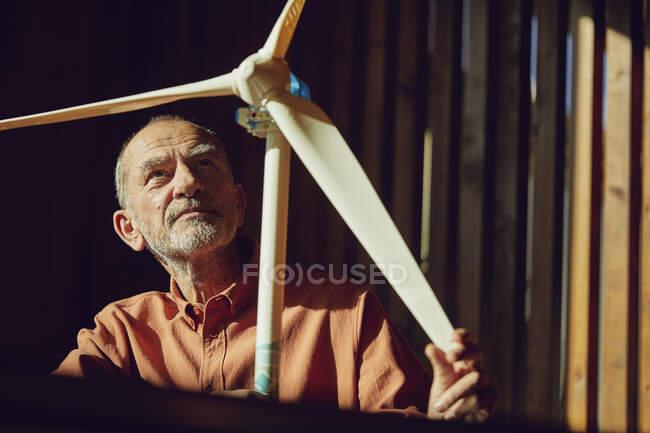 Ingeniero senior trabajando en soluciones de energía eólica, mirando turbina eólica - foto de stock