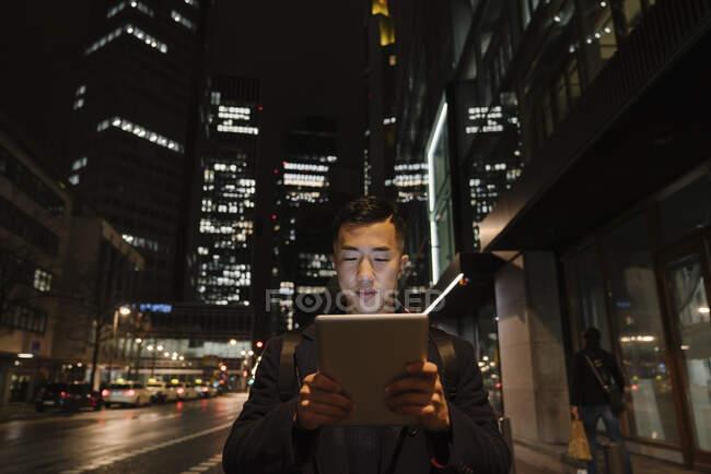 Hombre usando tableta en la ciudad por la noche - foto de stock