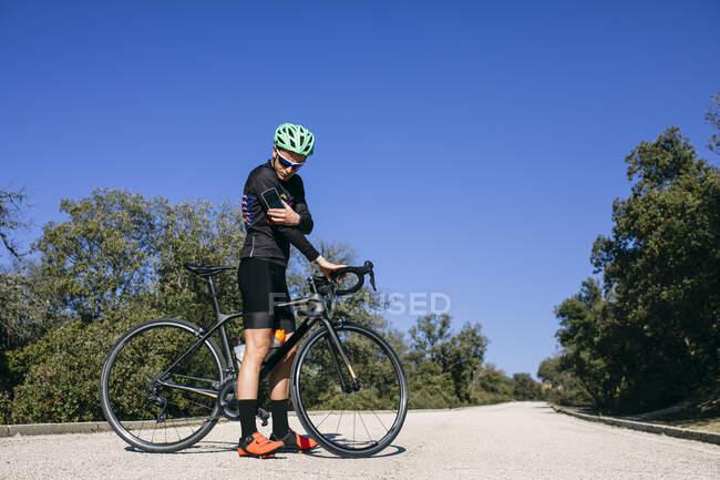 Велосипедист - діабетик перевіряє рівень цукру під час перерви на сільській дорозі. — стокове фото