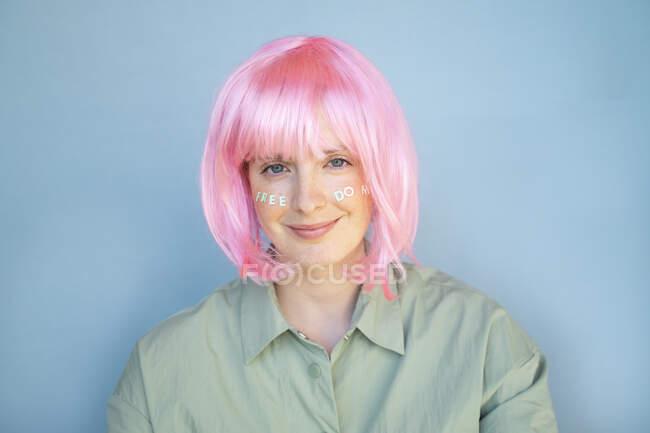 Молодая женщина в розовом парике, письма на лице, свобода — стоковое фото