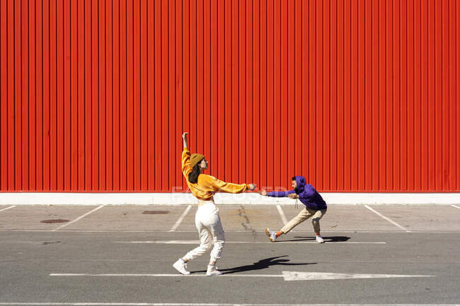 Young man and woman performing in front of a red wall — стоковое фото