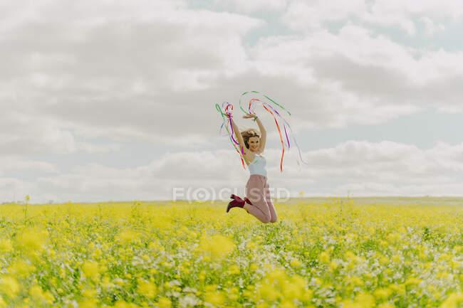 Feliz joven saltando con cintas de colores en un prado de flores en primavera - foto de stock