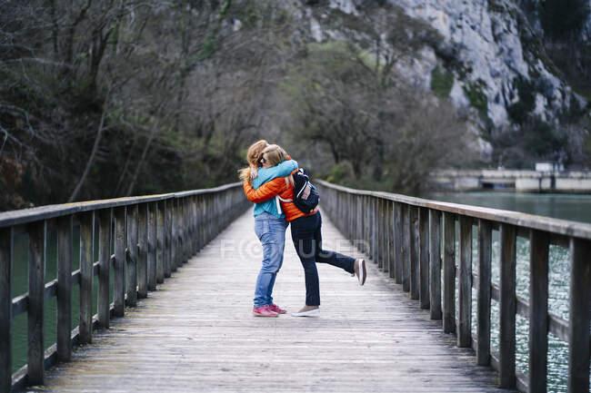 Дві щасливі жінки стоять на набережній, обіймаючи одне одного, водосховище вальне, астурії, — стокове фото