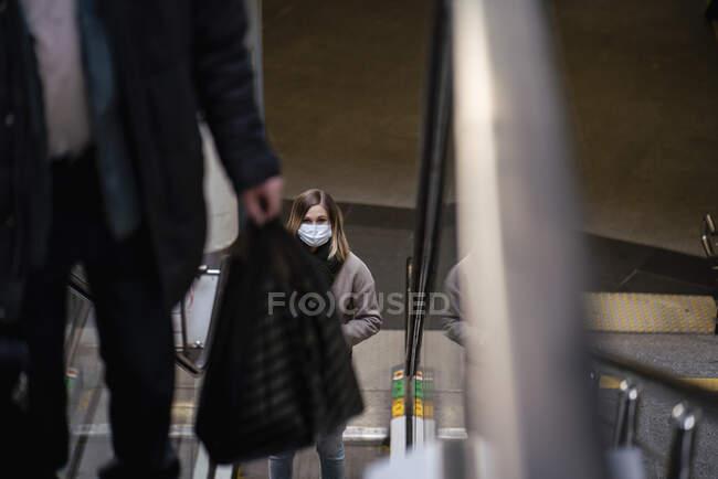Mujer con máscara facial en escalera mecánica en la estación de tren - foto de stock