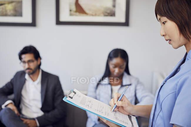 Formulario de comprobación de la recepcionista en la sala de espera de una consulta dental - foto de stock