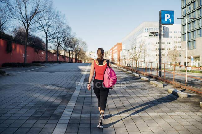 Jovem esportiva com prótese de perna andando no parque de estacionamento da cidade — Fotografia de Stock