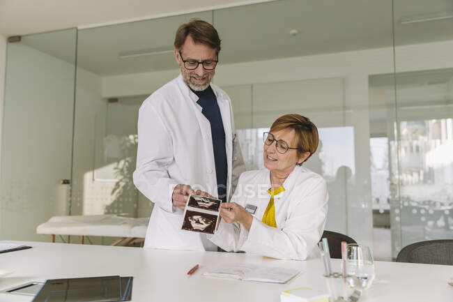Two doctors discussing ultrasound images of fetus — Stock Photo