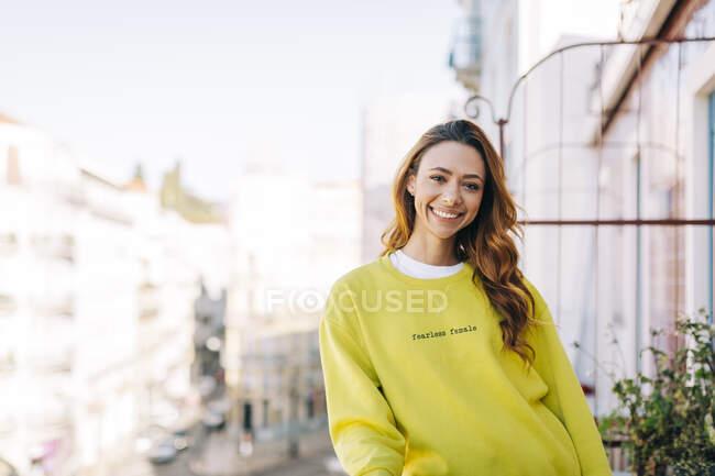 Portrait de jeune femme heureuse debout sur le balcon — Photo de stock
