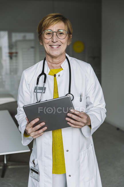 Ritratto di medico sorridente che tiene in mano la compressa — Foto stock