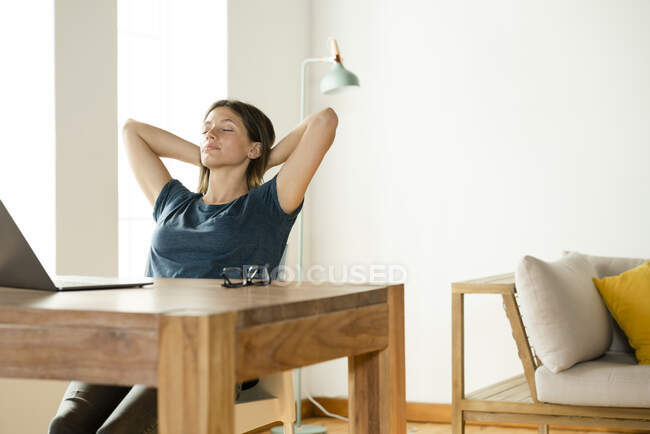 Молода жінка вдома відпочиває і відпочиває від роботи в ноутбуці в домашньому офісі. — стокове фото