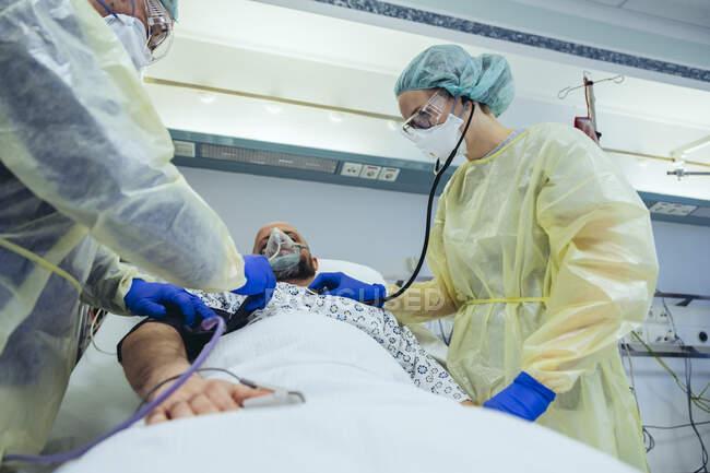 Médicos que atendem pacientes em unidade de pronto atendimento de um hospital com equipamentos respiratórios — Fotografia de Stock