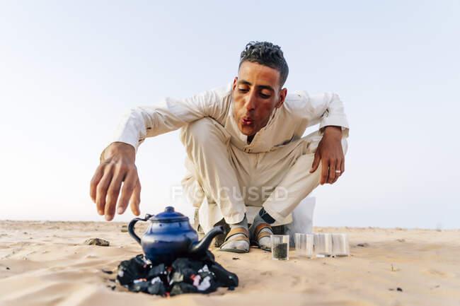 Человек готовит чай в пустыне Сахара, Тиндуф, Алжир — стоковое фото