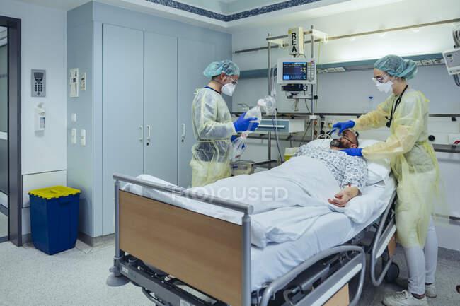 Лікарі, які доглядають за пацієнтом у відділенні невідкладної допомоги, змінюють дихання від кисневої маски до мішкувальної маски. — стокове фото