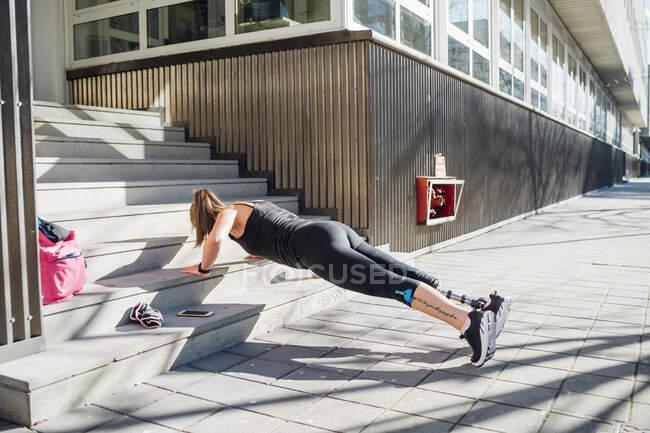 Спортивная молодая женщина с протезом для ног, тренирующаяся на лестнице в городе — стоковое фото