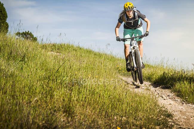 Mujer montada en bicicleta de montaña por el sendero frente al cielo azul, Santa Cruz, California, EE.UU. - foto de stock