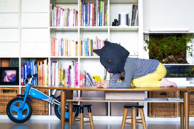 Little girl kneeling on table, imitating cat, using smartphone — Stock Photo