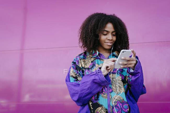 Mujer joven escribiendo en el teléfono inteligente y escuchando música - foto de stock