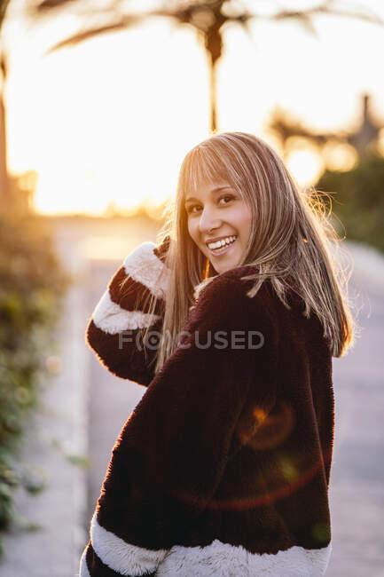Jovem mulher vestindo casaco de pele andando na rua durante o pôr do sol — Fotografia de Stock