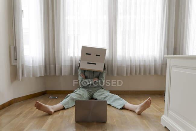 Mujer con una caja de cartón en la cabeza con sonrisa aburrida sentada en el suelo y mirando a la computadora portátil - foto de stock