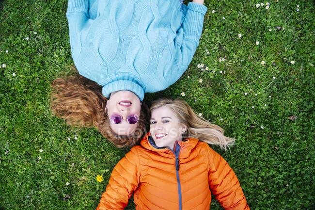 Retrato de dos amigos felices acostados en un prado - foto de stock