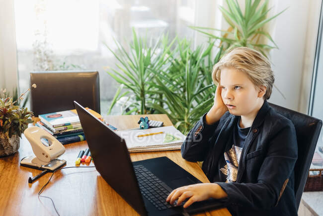 Frustrated boy sitting at desk with laptop — Stock Photo