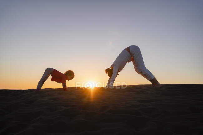Мати і дочка практикують йогу в піщаних дюнах на заході сонця (Гран - Канарія, Іспанія). — стокове фото